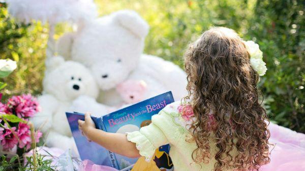Niña leyendo libro a sus muñecos