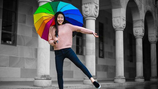 mujer sonriente con paraguas de colores