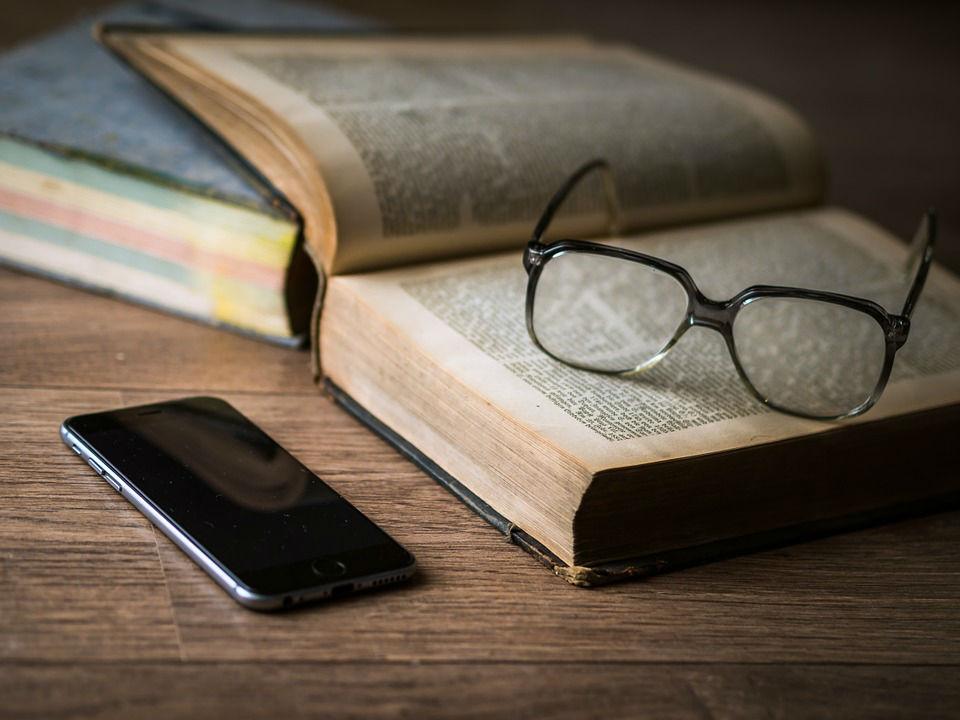 libro, celular y lentes sobre mesa de madera