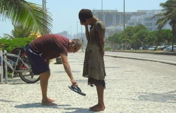 hombre ofrece sus zapatos a niña descalza