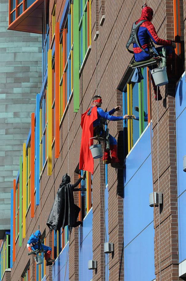 Limpiadores de ventanas vestidos de súperheroes